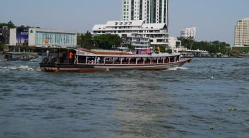 An Express Boat Traveling Along The Chao Phraya River In Bangkok