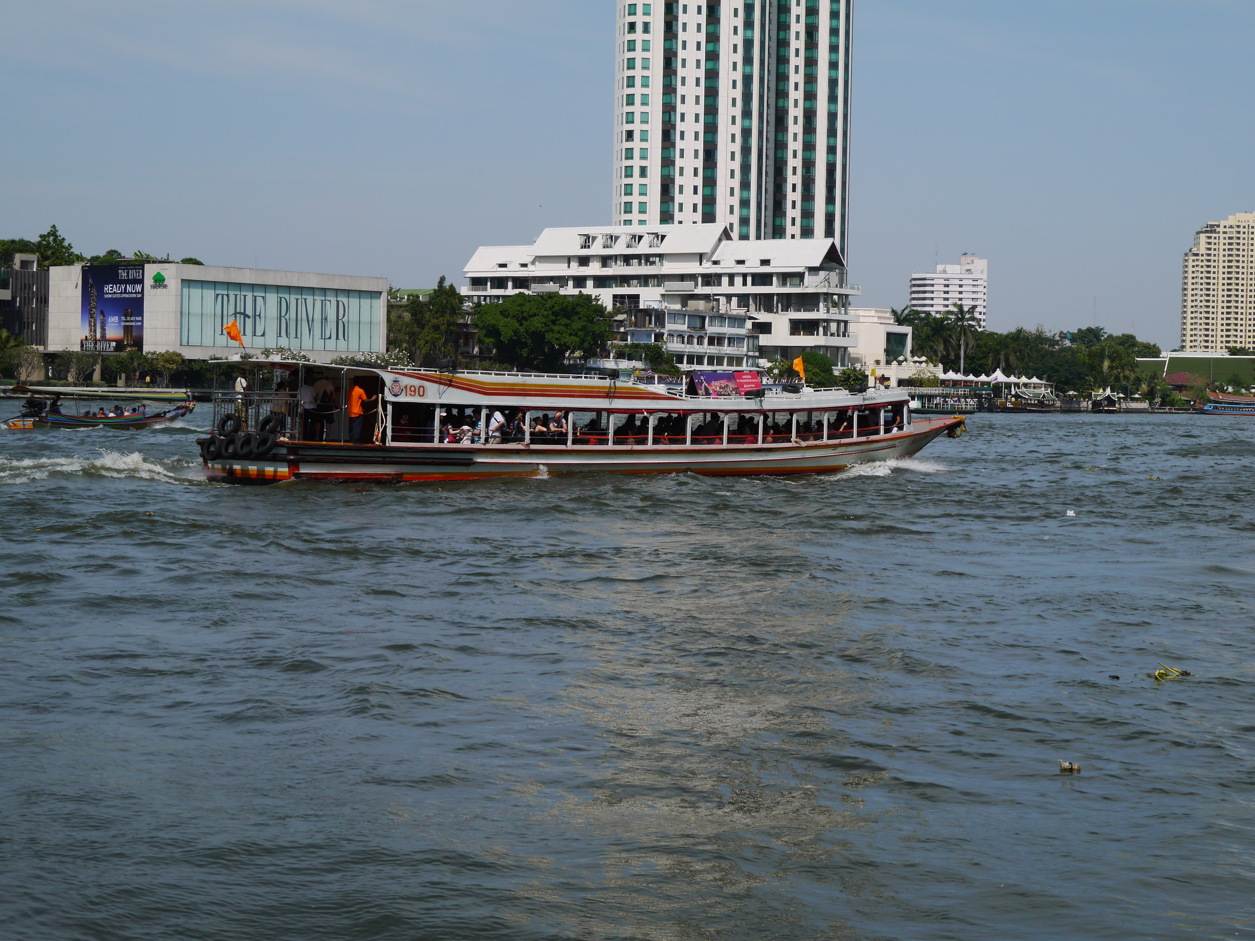 An Express Boat Traveling Along The Chao Phraya River In Bangkok