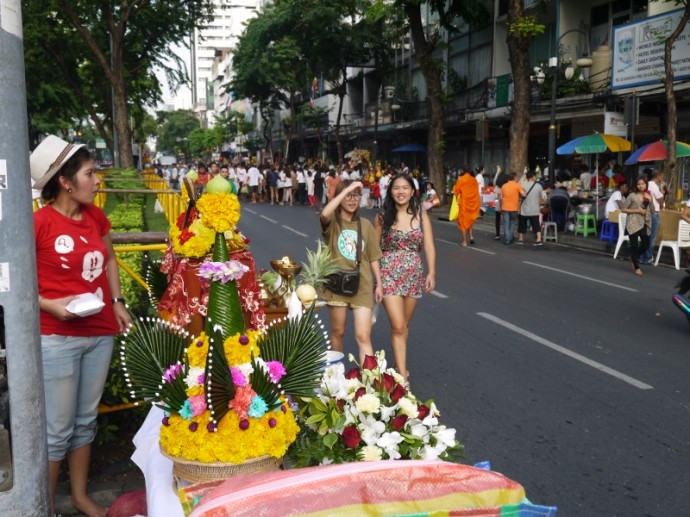 Two Girls Walk Passed A Shrine On Silom Road