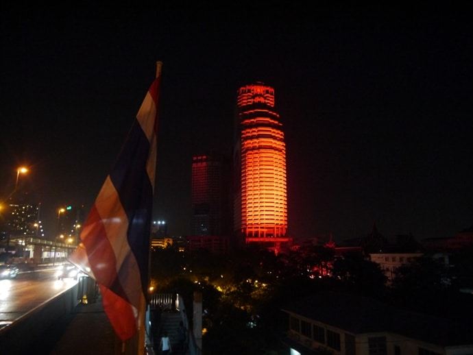 View From Taksin Bridge, With Thai Flagm And Traffic Rushing Passed